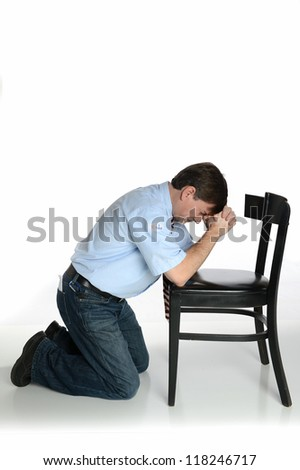 "Man with ""I Voted"" Sticker kneels in prayer, isolated on white - stock photo"