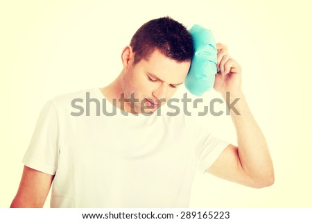 Man with ice bag for headaches, migraines ,hangover and injury - stock photo