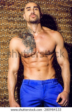 man with impressive press and tattoo poses in blue pants - stock photo