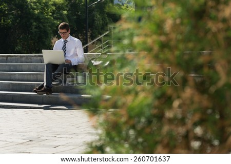 Man with laptop at summer park on bright day - stock photo