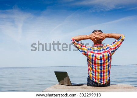 Man with laptop enjoy outdoor working - stock photo