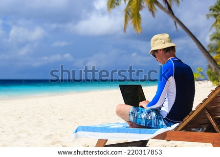 man with laptop on tropical beach vacation - stock photo
