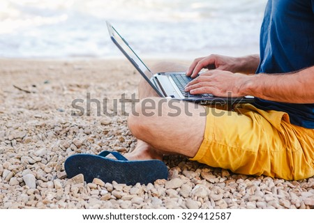 man with laptop working on colorful beach - stock photo