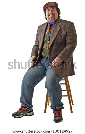 Man with large build sits on stool, dressed casually in tweed cap, jacket and jeans. He leans back and laughs. Vertical, isolated on white background, copy space. - stock photo