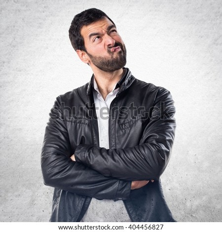 Man with leather jacket having doubts - stock photo