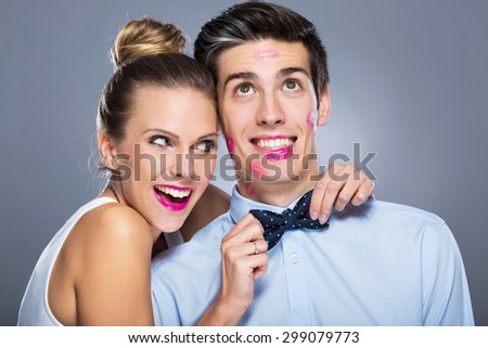 Man with lipstick marks and smiling woman  - stock photo