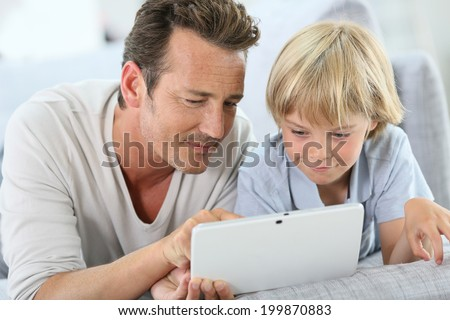 Man with little boy playing with digital tablet - stock photo