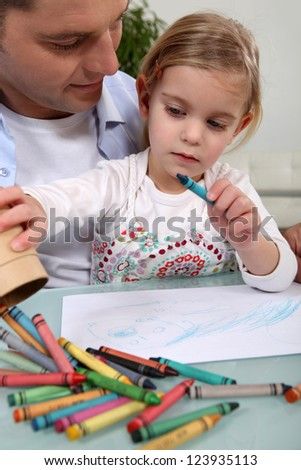 Man with little girl colouring - stock photo