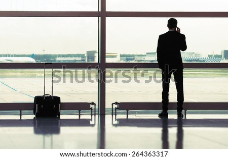 Man with luggage in the airport - stock photo
