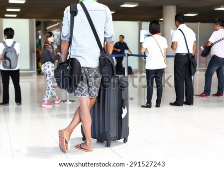 Man with luggage standing waiting for arrival passanger in the airport with crowd on background - stock photo