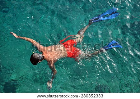 Man with mask snorkeling and in clear water - stock photo