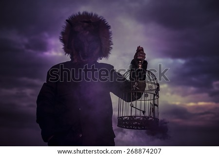 man with mask wolf cage at sunset, dreams and nightmares - stock photo