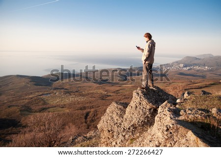Man with mobile phone on top of a mountain. - stock photo