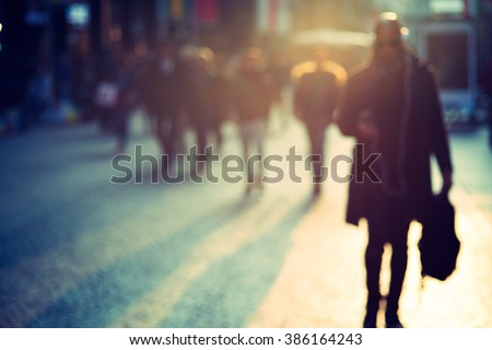 man with mobile phone walking in the street, technology concept, blurry - stock photo