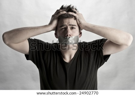 Man with mouth covered by masking tape preventing speech. - stock photo