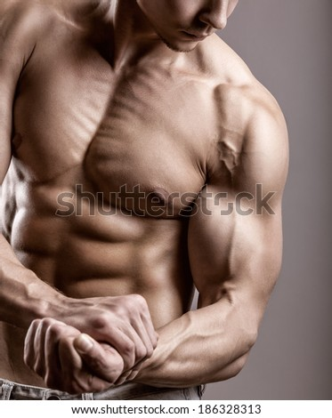 Man with muscular arms on a gray background - stock photo