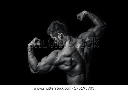 Man with muscular torso isolated on black background,  male torso with lights showing muscle detail, sports guy with a naked torso, The beautiful and strong young guy - stock photo