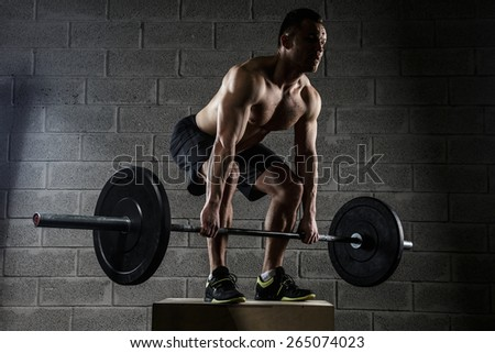 Man with naked torso holds barbell over the grey wall - stock photo