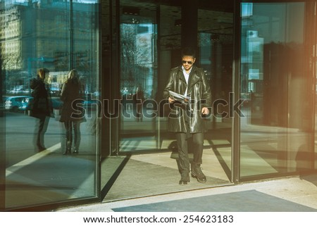 Man with newspaper in hand walks out of doors outdoors - stock photo