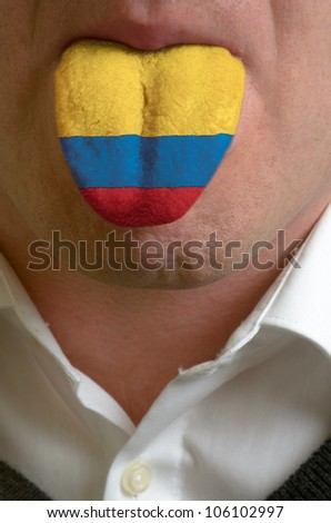 man with open mouth spreading tongue colored in colombia flag as symbol of values like teaching, learning, multilingual speaking of different languages - stock photo