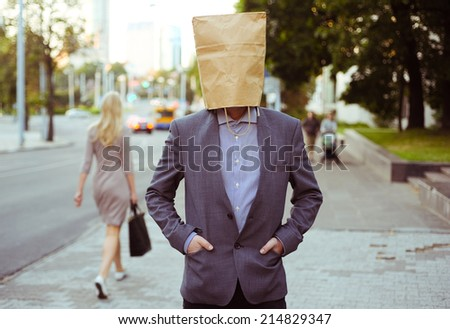 Man with paper bag on the head in the street - stock photo