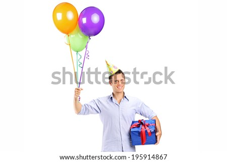 Man with party hat holding balloons and a present isolated on white background - stock photo