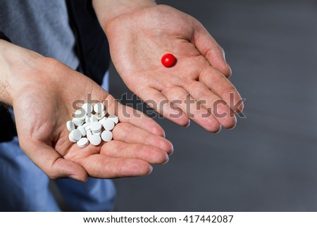Man with pile of white pills in one hand and a red pill in another - stock photo
