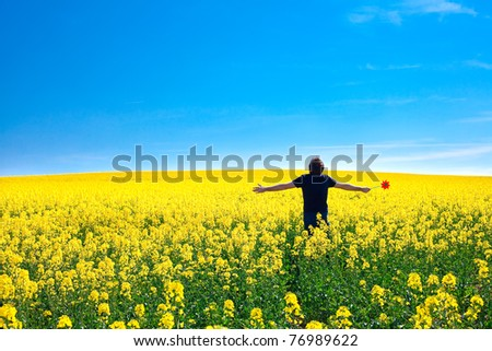 man with pinwheel standing in a field of yellow rapeseed against the blue sky - stock photo