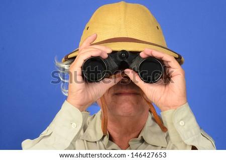 Man with pit helmet glasses and binoculars/Safari Man/ Man is using his binoculars to search - stock photo