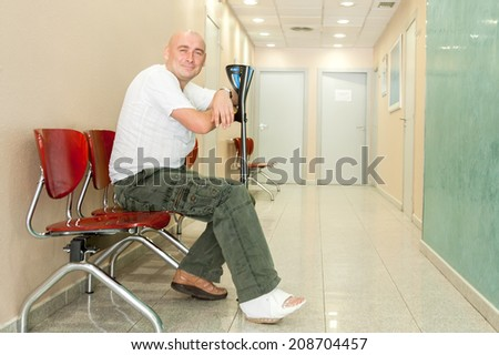man with  plaster on his leg sits in  hospital corridor - stock photo