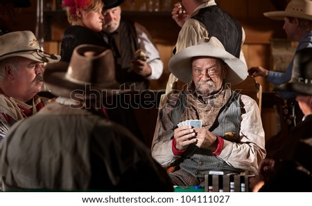 Man with poker face in American old west scene - stock photo