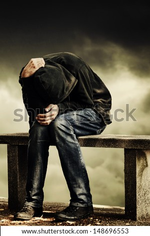 Man with problems. Man in hood with hands on his head sitting on the concrete bench. Drug addict concept. - stock photo