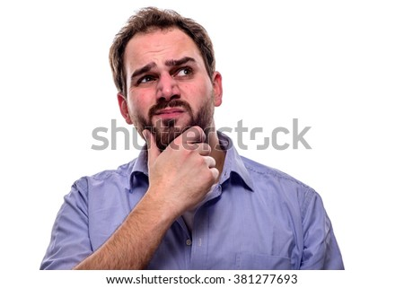 Man with questioning look in his eyes and hand on his chin - stock photo