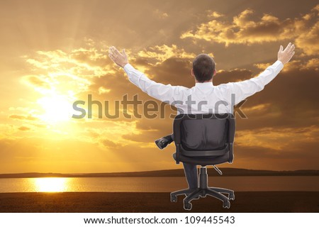 Man with raised hands sitting on chair on asphalt road on orange sunset - stock photo