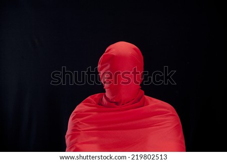 Man with red coat on black background - stock photo