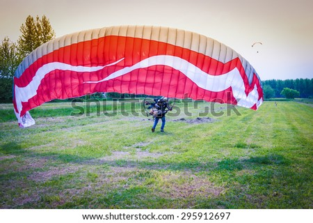 man with red motorized paraglider takes off from a green field - stock photo