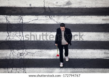 Man with red roses crossing the street - stock photo