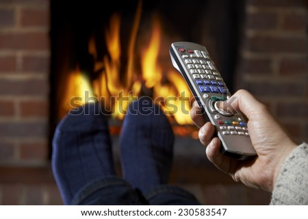 Man With Remote Control Watching Television And Relaxing By Fire - stock photo