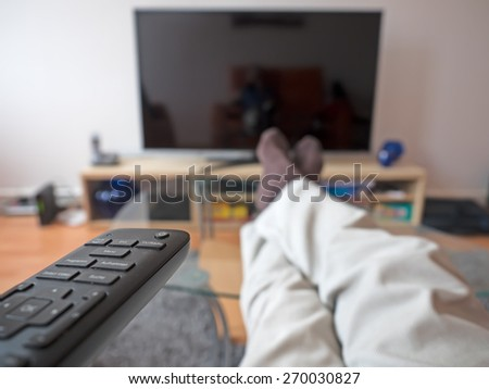 Man with remote control watching TV - stock photo