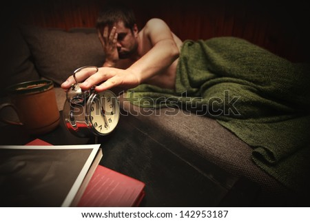 man with sad expression touch clock in early morning - stock photo