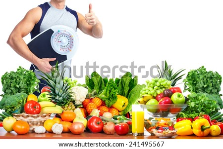 Man with scales fruits and vegetables background - stock photo