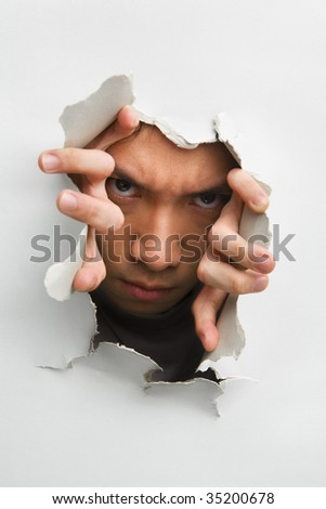 Man with scary look from cracked wall - one of the breakthrough series - stock photo
