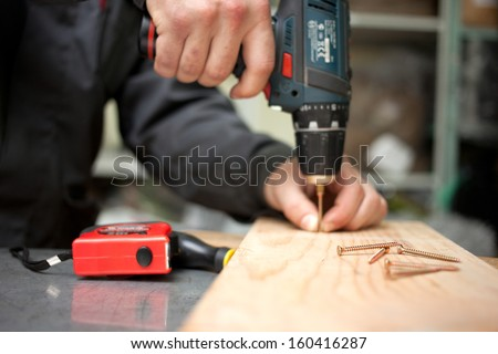 Man with screwdriver. Focused on screw in front. Clouseup concept - stock photo
