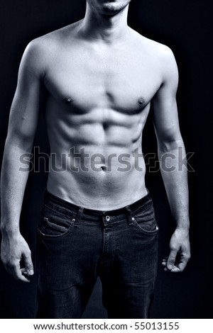 Man with sexy muscular ripped abdomen over black - stock photo