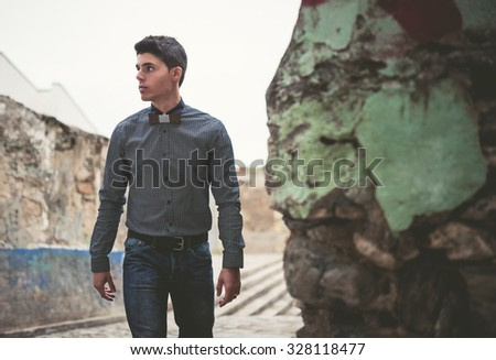 Man with shirt and jeans walking down the street - stock photo