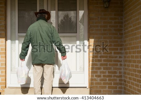 Man with shopping bags at the door - stock photo