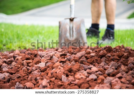 Man with shovel soft in behind fresh new lava stone in the garden. Great backdrop for a gardening theme - stock photo