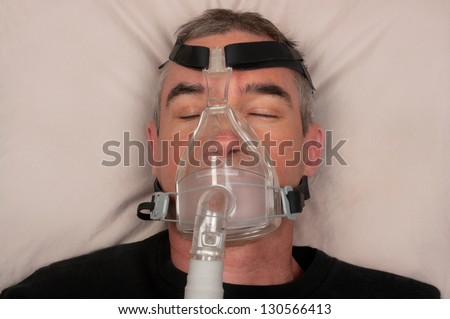 Man with sleep apnea and CPAP machine - stock photo