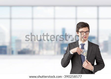 Man with sly look putting one hundred dollar banknotes into the chest pocket. Blurred office at background. Concept of getting rich. - stock photo