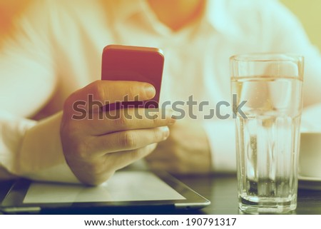 Man with smart phone in hand, blurred background, glass of wather - stock photo